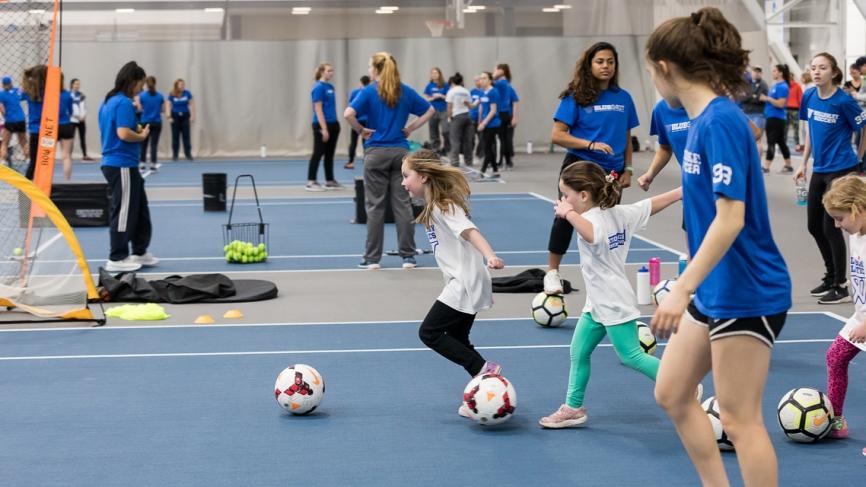 Young girls dribble soccer balls