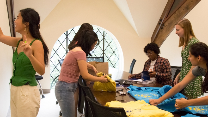 Six students fold t shirts in an office space.