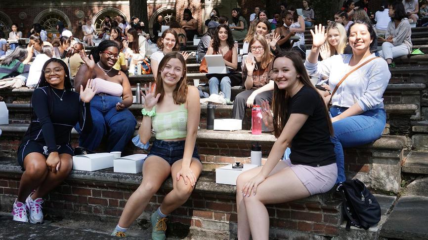 students smiling and waving at camera