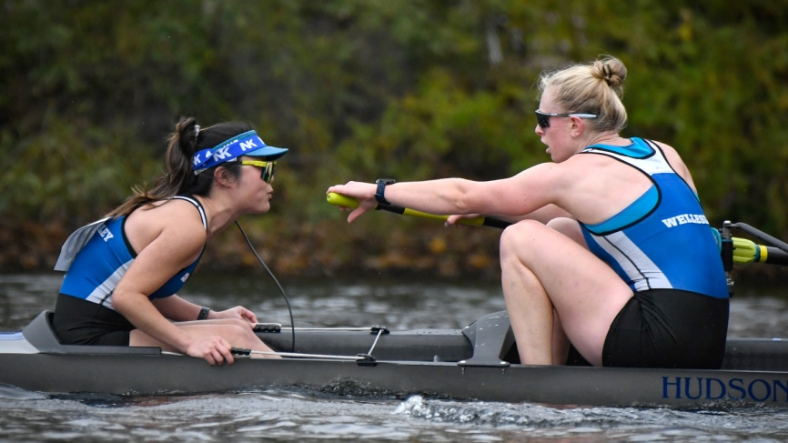 A coxswain and rower sit facing each other in a boat during a race.