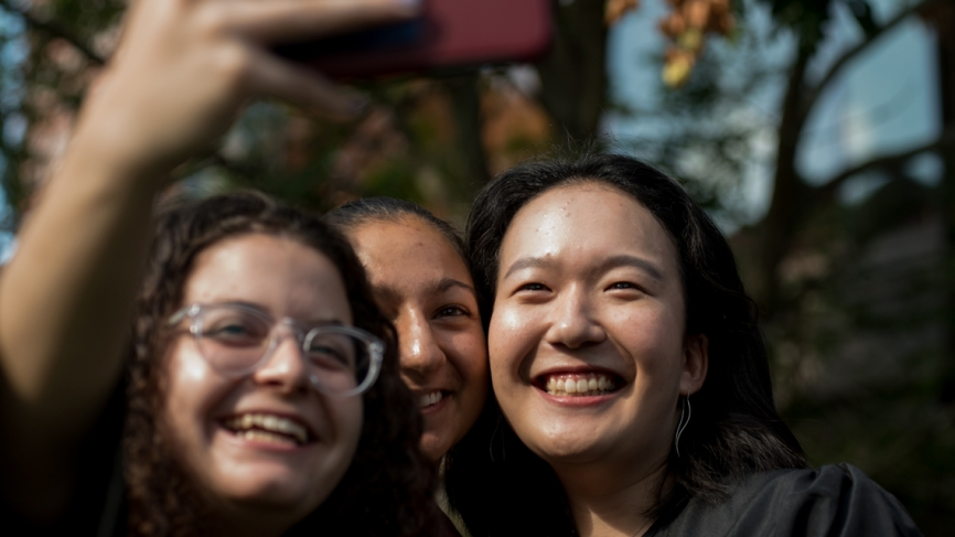 Three students celebrate Convocation with a selfie in front of Alumnae Auditorium.