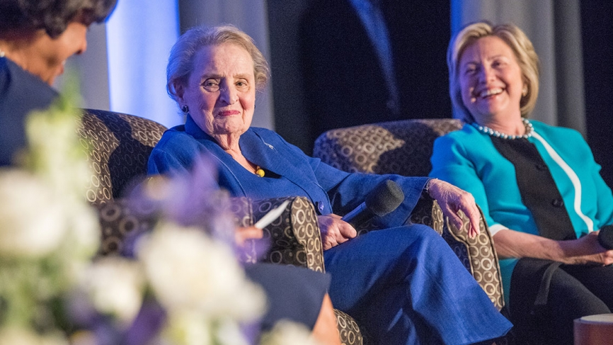 Hillary Clinton and Madeleine Albright sit on a stage with President Johnson