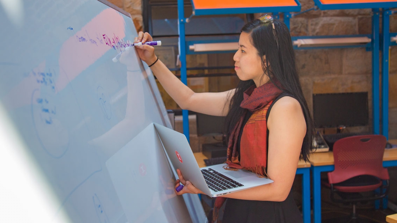 A student stands by a white board, writing and holding a computer