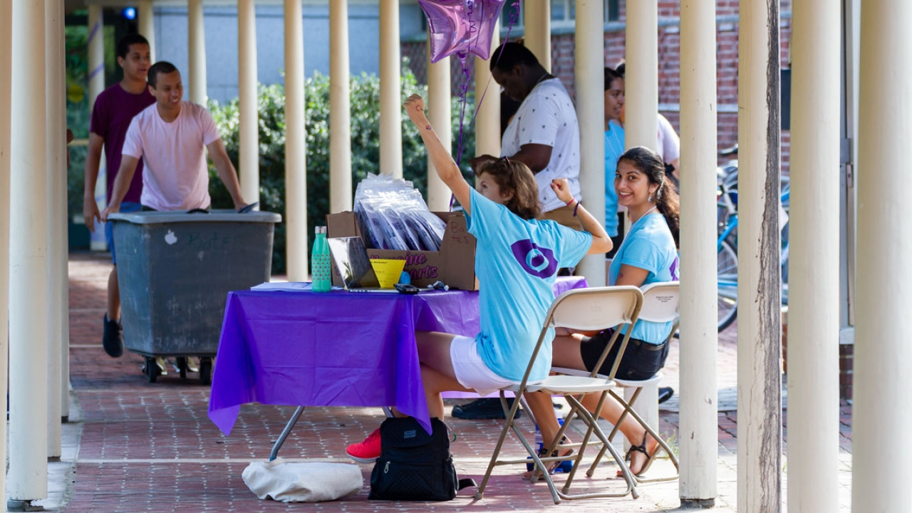 Two student leaders sit at a table checking in first year students while families and students move in around them.