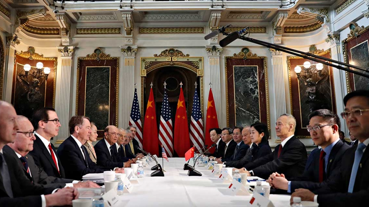 Diplomats sit around a large table.