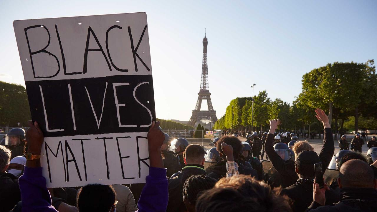 Black Lives Matter sign being held up in front of the Eiffel Tower