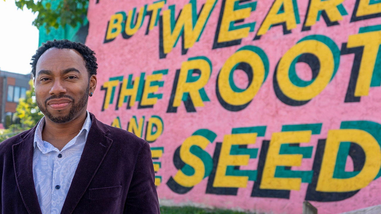 "A professor stands in front of public art that reads ""we are the root and the seed."""