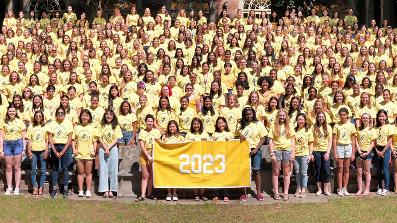 The class of 2023's class photo. They wear yellow shirts and hold a yellow banner.