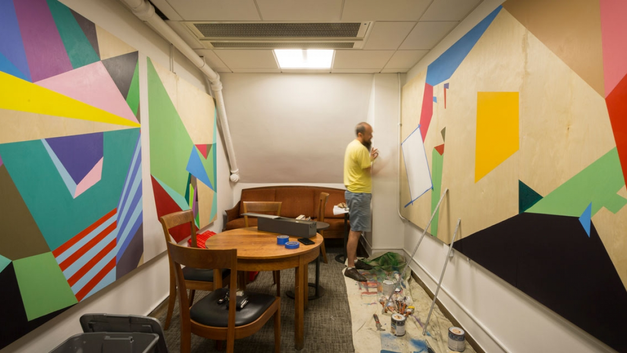 A Wellesley Professor paints a wall-sized mural.