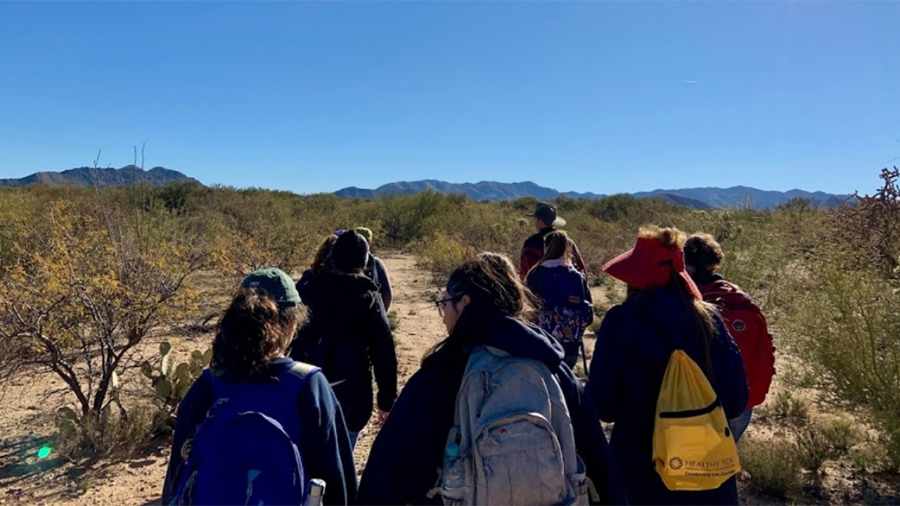 Students walk through a desert in Arizona.