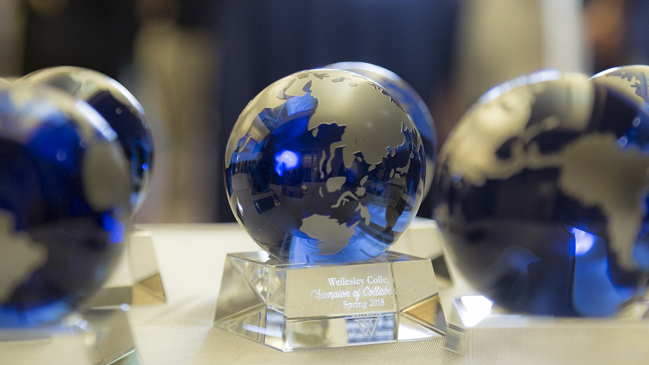 Faculty and staff recognition awards shaped as a globe sit on a table.
