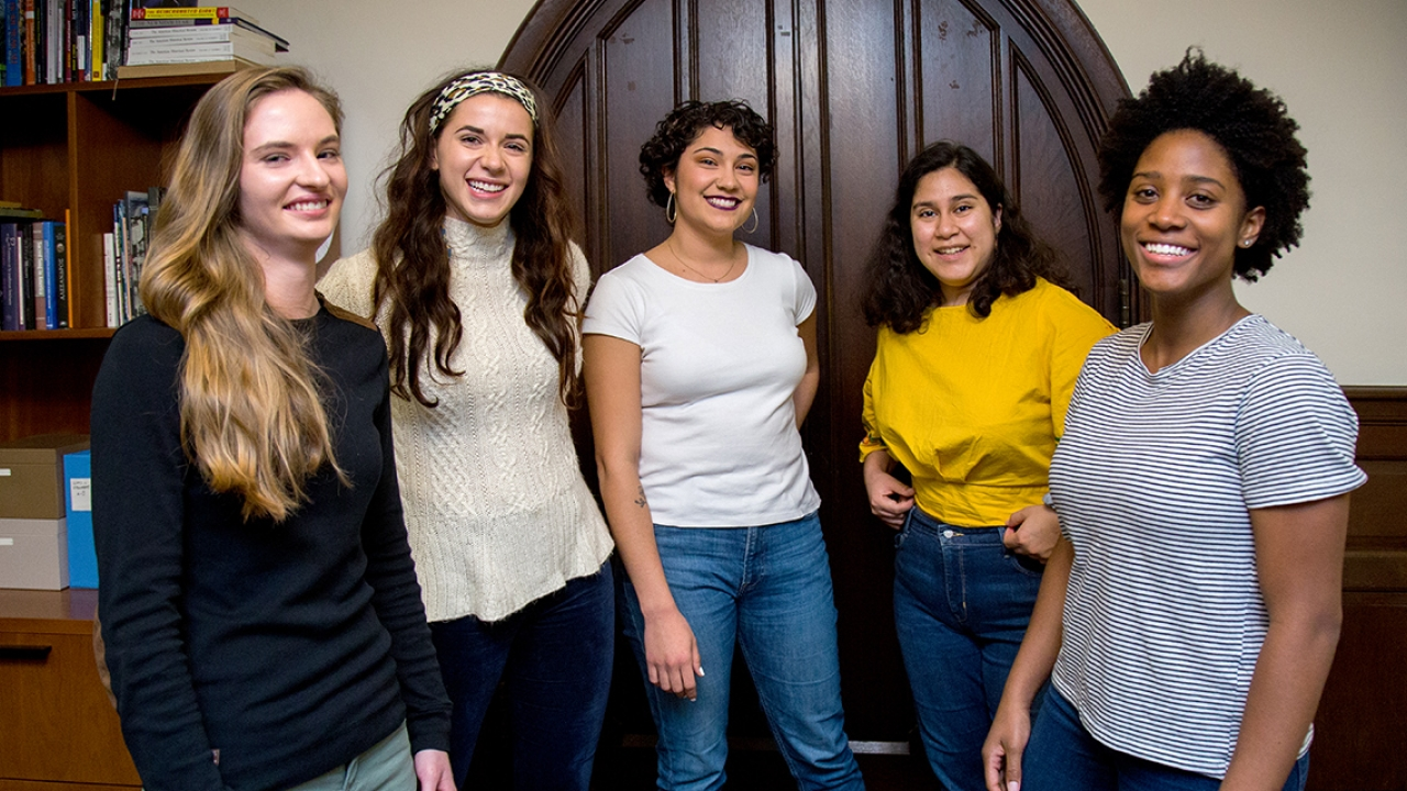 Five student pose in front of a door in the Provosts Office