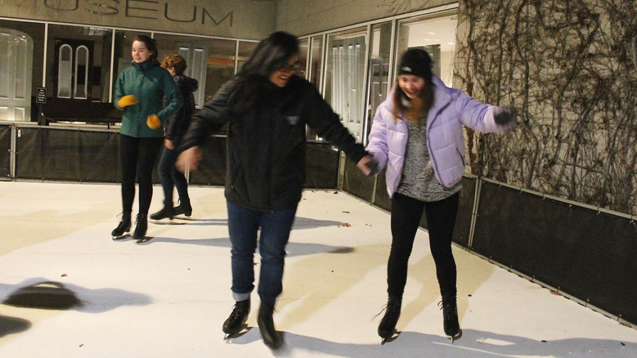 Two students ice skate on Davis Plaza