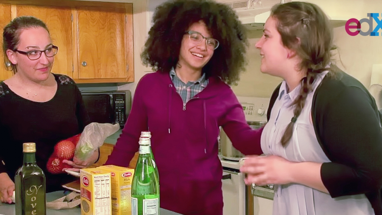 Three women stand around a table before cooking