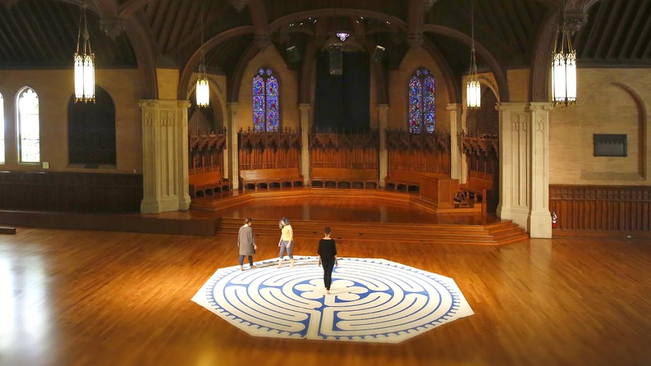 Three women walk a labyrinth inside Houghton Chapel.