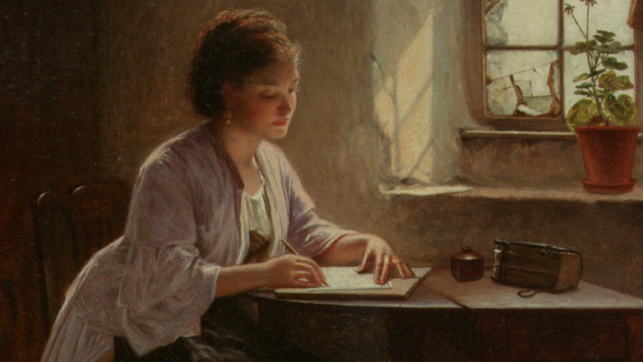 A woman sits at a desk, writing.