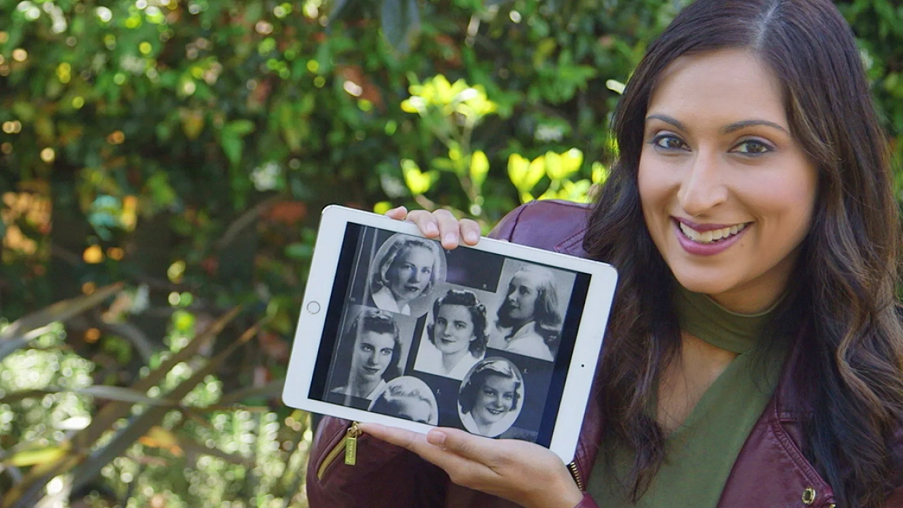 A woman holds an iPad with old photos of women.