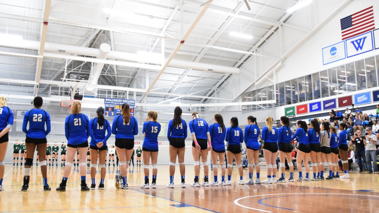 The Wellesley volleyball teams stands on the court before a game.