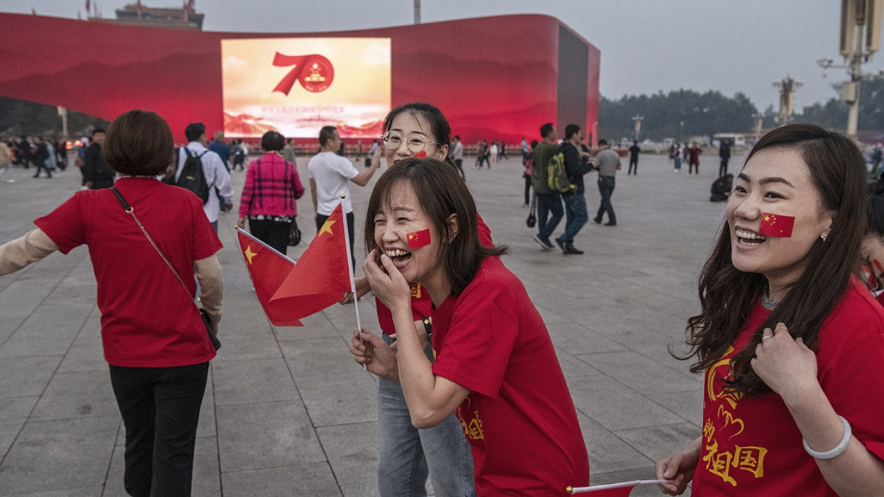 Chinese tourists wear 70th anniversary t-shirts as they stand near a large screen set up for the 70th National Day celebrations