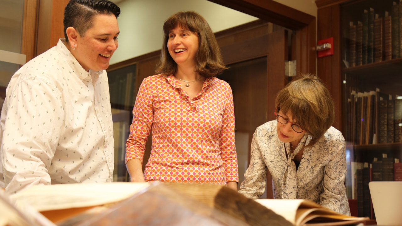 Three members of the archives and special collections staff look at a book.