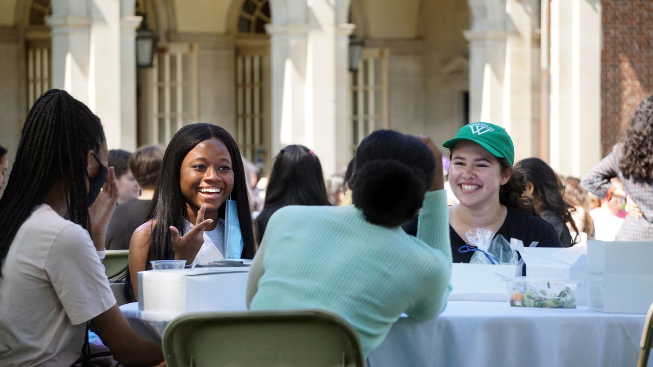 students smiling and eating together at an outdoor table