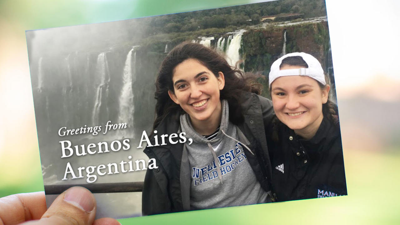 "On a postcard, two students stand in front of a waterfall in Buenos Aires. It reads, ""Greetings from Buenos Aires, Argentina!"""