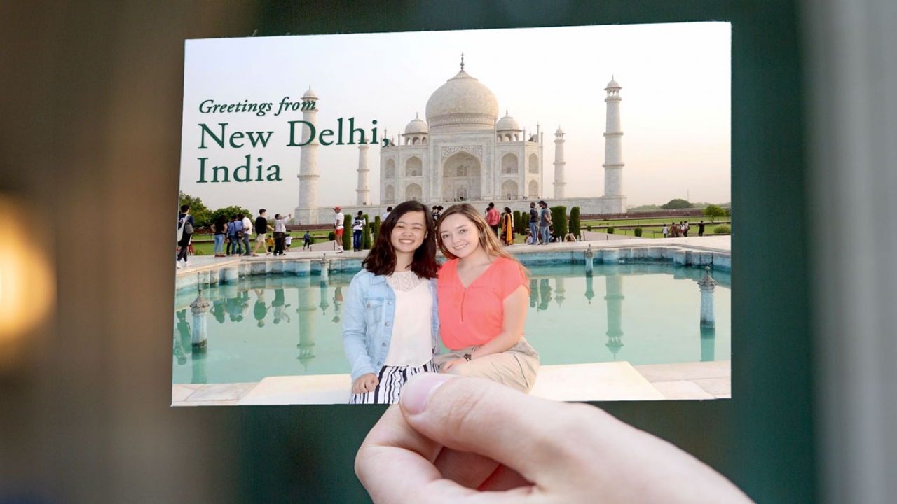 students smiling and standing in front of Taj Mahal