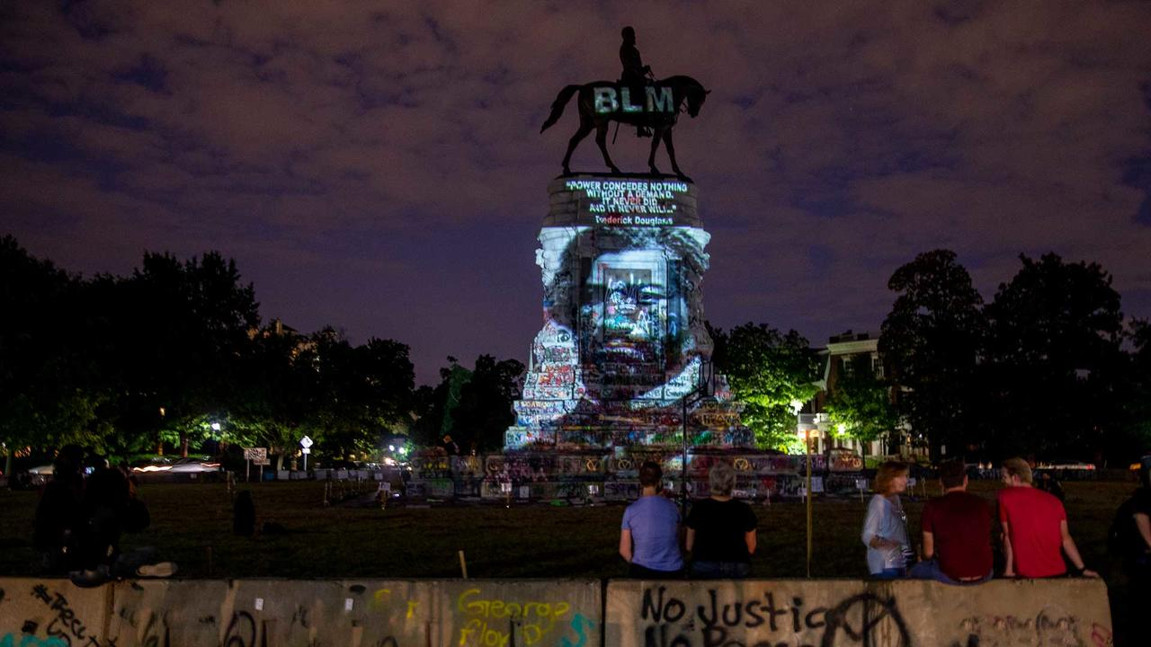 Frederick Douglass' image is projected on the Robert E. Lee Monument