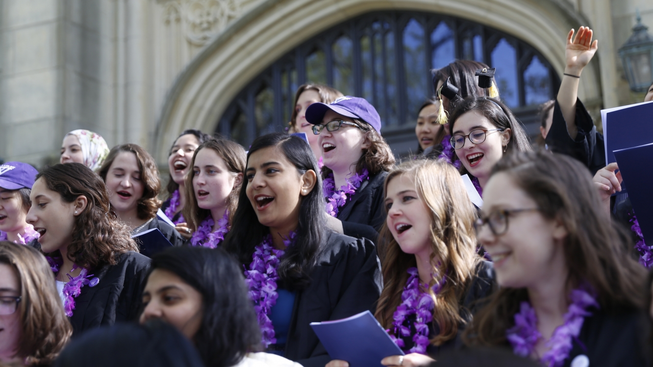 Members of the Class of 2018 sing on the steps of Houghton Chapel at Wellesley College.