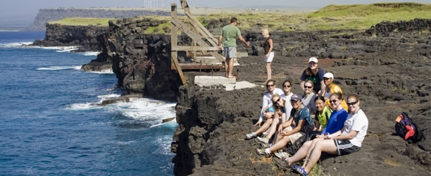 Students sit on cliff in SouthPoint Hawaii